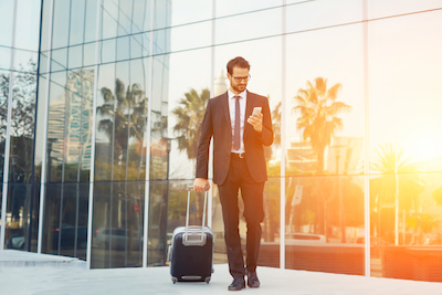 9 Airbnb, AI, and Additional Insights into Travel Marketing Trends This Week: Traveler booking on his mobile phone