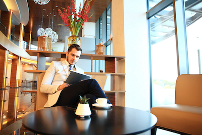 Chatbots, AI and all the hospitality digital marketing trends: Man using tablet in hotel lobby